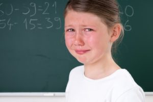 verzweifelte Schülerin an der Tafel mit Mathe-Aufgaben