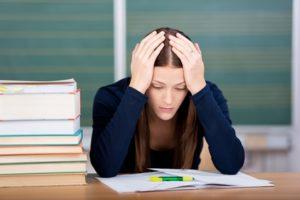 Studentin sitzt verzweifelt über ihren Lernunterlagen