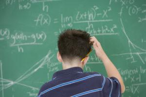 Verzweifelter Bub an Tafel mit Mathe-Aufgaben