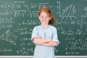 Selbstbewusstes Mädchen vor Tafel mit Mathe-Aufgaben