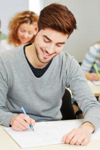 Junger Mann schreibt Matura-Prüfung